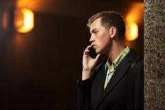 Νέο επιχειρησιακό άτομο που καλεί το κινητό τηλέφωνο στον τοίχο Στοκ φωτογραφία με δικαίωμα ελεύθερης χρήσης
