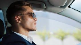 Νέο επιχειρησιακό άτομο που φορά τα γυαλιά ηλίου καθμένος σε ένα αυτοκίνητο Κάθεται πίσω από τη ρόδα Έννοια της επιτυχίας, σταδιο απόθεμα βίντεο