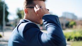 Νέο επιχειρησιακό άτομο που φορά τα γυαλιά ηλίου που περπατούν έξω Εξετάζει τη κάμερα, σε αργή κίνηση Πυροβοληθείς στο κόκκινο έπ απόθεμα βίντεο