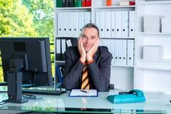 Νέο επιχειρησιακό άτομο στο γραφείο του που φαίνεται φιλικό Στοκ Εικόνα