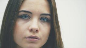 Νέο επιχειρησιακό κορίτσι που στέκεται σε ένα άσπρο υπόβαθρο Κατά τη διάρκεια αυτού, κοιτάζει στη κάμερα με τα όμορφα μπλε μάτια φιλμ μικρού μήκους