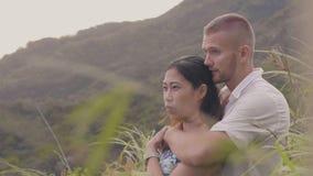 Νέο ερωτευμένο αγκάλιασμα ζευγών και φίλημα στο πράσινο τοπίο βουνών Ευτυχείς άνδρας και γυναίκα που αγκαλιάζουν και που απολαμβά απόθεμα βίντεο