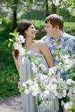 Νέο ερωτευμένο περπάτημα ζευγών στον κήπο άνοιξη ανθών Στοκ Φωτογραφίες