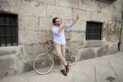 Νέο ευτυχές άτομο που παίρνει selfie με το κινητό τηλέφωνο στο αναδρομικό δροσερό εκλεκτής ποιότητας ποδήλατο Στοκ εικόνα με δικαίωμα ελεύθερης χρήσης