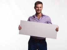 Νέο ευτυχές άτομο που παρουσιάζει παρουσίαση, που δείχνει στην αφίσσα Στοκ Εικόνες