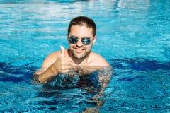 Νέο ευτυχές άτομο που φορά τα γυαλιά ηλίου στο gesturin πισινών Στοκ φωτογραφίες με δικαίωμα ελεύθερης χρήσης