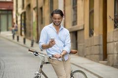 Νέο ευτυχές άτομο που χαμογελά χρησιμοποιώντας το κινητό τηλέφωνο στο εκλεκτής ποιότητας δροσερό αναδρομικό ποδήλατο Στοκ εικόνες με δικαίωμα ελεύθερης χρήσης