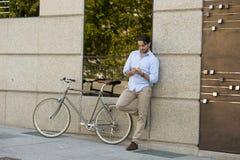 Νέο ευτυχές άτομο που χαμογελά χρησιμοποιώντας το κινητό τηλέφωνο στο εκλεκτής ποιότητας δροσερό αναδρομικό ποδήλατο Στοκ φωτογραφία με δικαίωμα ελεύθερης χρήσης