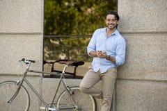 Νέο ευτυχές άτομο που χαμογελά χρησιμοποιώντας το κινητό τηλέφωνο στο εκλεκτής ποιότητας δροσερό αναδρομικό ποδήλατο Στοκ Εικόνα