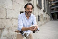 Νέο ευτυχές άτομο που χαμογελά χρησιμοποιώντας το κινητό τηλέφωνο στο εκλεκτής ποιότητας δροσερό αναδρομικό ποδήλατο Στοκ Φωτογραφία