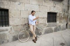 Νέο ευτυχές άτομο που χαμογελά χρησιμοποιώντας το κινητό τηλέφωνο στο εκλεκτής ποιότητας δροσερό αναδρομικό ποδήλατο Στοκ Εικόνες