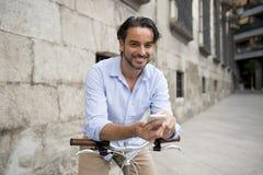 Νέο ευτυχές άτομο που χαμογελά χρησιμοποιώντας το κινητό τηλέφωνο στο εκλεκτής ποιότητας δροσερό αναδρομικό ποδήλατο Στοκ εικόνα με δικαίωμα ελεύθερης χρήσης