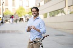 Νέο ευτυχές άτομο που χαμογελά χρησιμοποιώντας το κινητό τηλέφωνο στο εκλεκτής ποιότητας δροσερό αναδρομικό ποδήλατο Στοκ φωτογραφίες με δικαίωμα ελεύθερης χρήσης