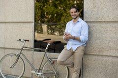 Νέο ευτυχές άτομο που χαμογελά χρησιμοποιώντας το κινητό τηλέφωνο στο εκλεκτής ποιότητας δροσερό αναδρομικό ποδήλατο Στοκ Φωτογραφίες