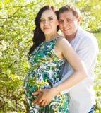 Νέο ευτυχές έγκυο ζεύγος στο ανθίζοντας πάρκο άνοιξη Στοκ φωτογραφία με δικαίωμα ελεύθερης χρήσης