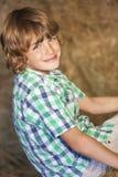 Νέο ευτυχές αγόρι που χαμογελά στα δέματα σανού Στοκ εικόνα με δικαίωμα ελεύθερης χρήσης