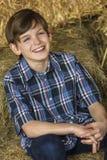Νέο ευτυχές αγόρι που χαμογελά στα δέματα σανού Στοκ Φωτογραφίες