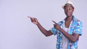 Νέο ευτυχές αφρικανικό άτομο τουριστών που δείχνει το δάχτυλο και που παρουσιάζει κάτι φιλμ μικρού μήκους