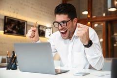 Νέο ευτυχές επιχειρησιακό άτομο που παρουσιάζει χειρονομία νικητών, που εξετάζει το lapt Στοκ Φωτογραφίες
