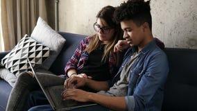 Νέο ευτυχές ζεύγος δύο hipsters που διατάζει τα τρόφιμα σε απευθείας σύνδεση, χρησιμοποιώντας το lap-top απόθεμα βίντεο