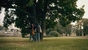 Νέο ευτυχές ζεύγος που έχει τη διασκέδαση στο πάρκο από κοινού Όμορφοι άνδρας και γυναίκα που τρέχουν στο δέντρο επειδή η βροχή τ φιλμ μικρού μήκους