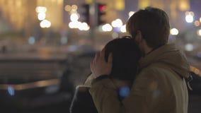 Νέο ευτυχές ζεύγος που αγκαλιάζει κατά την ημερομηνία, που απολαμβάνει τη θέα πόλεων νύχτας, σχέση απόθεμα βίντεο