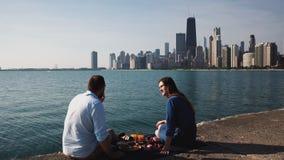Νέο ευτυχές ζεύγος που απολαμβάνει τη ρομαντική ημερομηνία στην ακτή της λίμνης του Μίτσιγκαν με την πανοραμική άποψη του Σικάγου φιλμ μικρού μήκους
