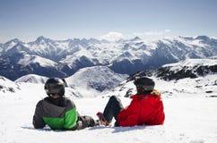 Νέο ευτυχές ζεύγος που βρίσκεται στα χιονώδη βουνά Στοκ Φωτογραφίες