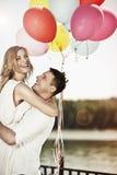 Νέο ευτυχές ζεύγος που κρατά ζωηρόχρωμα ballons και το αγκάλιασμα Στοκ Εικόνα