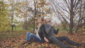 Νέο ευτυχές ζεύγος που παίζει και που ρίχνει τα φύλλα στο πάρκο φθινοπώρου απόθεμα βίντεο