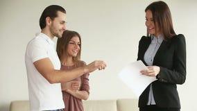 Νέο ευτυχές ζεύγος που παίρνει τα κλειδιά από το καινούργιο σπίτι απόθεμα βίντεο