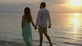 Νέο ευτυχές ζεύγος που περπατά κοντά στη θάλασσα στο ηλιοβασίλεμα Έννοια της αγάπης φιλμ μικρού μήκους