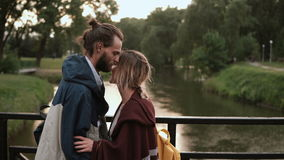 Νέο ευτυχές ζεύγος που περπατά στο πάρκο με τον ποταμό στο ηλιοβασίλεμα Όμορφο αγκάλιασμα ανδρών και γυναικών, συζήτηση στη γέφυρ απόθεμα βίντεο