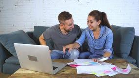 Νέο ευτυχές ζεύγος που πληρώνει τους λογαριασμούς με το lap-top φιλμ μικρού μήκους