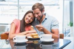 Νέο ευτυχές ζεύγος που τρώει το κέικ από κοινού Στοκ Εικόνες