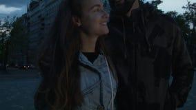 Νέο ευτυχές ζεύγος των τουριστών στο αντίθετο χαμόγελο οικοδόμησης νύχτας Όμορφος νεαρός άνδρας με μια γυναίκα στην πόλη απόθεμα βίντεο