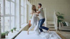 Νέο ευτυχές και αγαπώντας ζεύγος που έχει την πάλη μαξιλαριών και που φιλά στο κρεβάτι στο σπίτι φιλμ μικρού μήκους