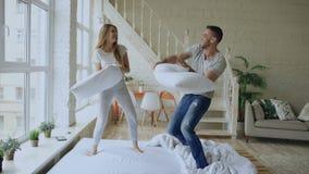 Νέο ευτυχές και αγαπώντας ζεύγος που έχει την πάλη μαξιλαριών στο κρεβάτι στο σπίτι απόθεμα βίντεο
