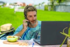 Νέο ευτυχές και ελκυστικό άτομο που εργάζεται υπαίθρια με το φορητό προσωπικό υπολογιστή και το κινητό τηλέφωνο ως ταξίδι Διαδικτ στοκ εικόνες