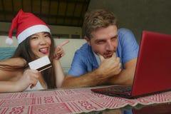 Νέο ευτυχές και συγκινημένο μικτό ζεύγος έθνους με την ασιατική κινεζική γυναίκα στο καπέλο Χριστουγέννων και τον καυκάσιο σύζυγο στοκ εικόνες