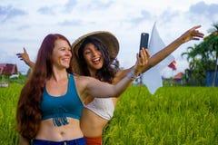 Νέο ευτυχές και όμορφο ισπανικό κορίτσι στο παραδοσιακό ασιατικό καπέλο αγροτών και καυκάσια γυναίκα που παίρνει τις φίλες selfie στοκ εικόνες