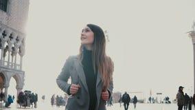 Νέο ευτυχές καυκάσιο κορίτσι τουριστών με το χαμόγελο σακιδίων πλάτης, που κοιτάζει γύρω από συγκινημένος στο παλαιό τετράγωνο ση απόθεμα βίντεο
