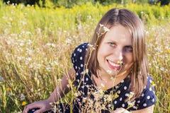 Νέο ευτυχές κορίτσι με την ανθοδέσμη στον τομέα μαργαριτών Στοκ εικόνα με δικαίωμα ελεύθερης χρήσης
