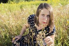 Νέο ευτυχές κορίτσι με την ανθοδέσμη στον τομέα μαργαριτών Στοκ Φωτογραφίες