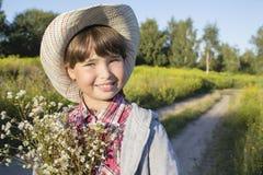 Νέο ευτυχές κορίτσι με την ανθοδέσμη στον τομέα μαργαριτών Στοκ εικόνες με δικαίωμα ελεύθερης χρήσης