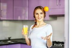 Νέο ευτυχές κορίτσι που πίνει το χυμό από πορτοκάλι για το θόριο γυναικών προγευμάτων Α Στοκ φωτογραφίες με δικαίωμα ελεύθερης χρήσης