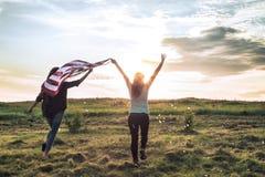 Νέο ευτυχές κορίτσι που τρέχει και που πηδά ξένοιαστο με τις ανοικτές αγκάλες πέρα από τον τομέα σίτου ΑΜΕΡΙΚΑΝΙΚΗ σημαία εκμετάλ στοκ φωτογραφία