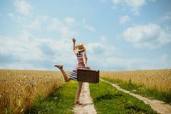 Νέο ευτυχές κορίτσι που φορά το ριγωτό φόρεμα που χορεύει επάνω Στοκ Εικόνες