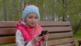 Νέο ευτυχές κορίτσι που χρησιμοποιεί το τηλέφωνο στο πάρκο σε σε αργή κίνηση φιλμ μικρού μήκους