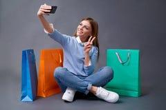 Νέο ευτυχές κορίτσι σπουδαστών με τις συσκευασίες που κάθεται στο πάτωμα στοκ φωτογραφίες